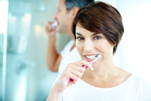 Woman and man brushing their teeth.